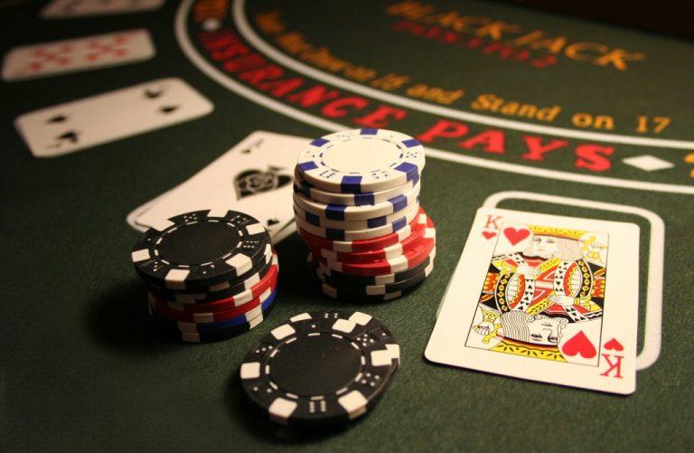Värillinen valokuva blackjack-korttipöydästä, jossa etualalla läjä erilaisia pelimerkkejä, ja kortteja.
